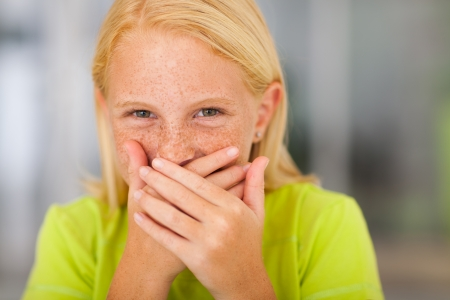 preteen: happy preteen girl covering her mouth and laughing