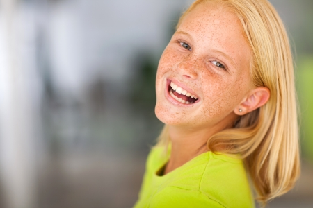 laughing preteen girl looking back headshot photo