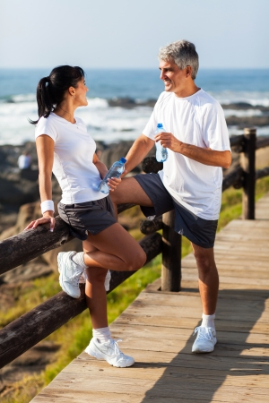 middle aged couple drinking water after exercising on beach photo