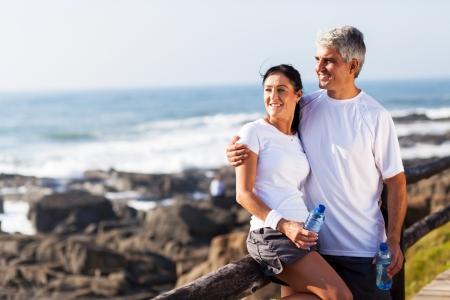 mature adult men: felice coppia matura di relax dopo l'attivit� fisica in spiaggia Archivio Fotografico