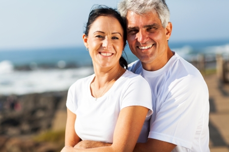 portrait of middle aged couple hugging at the beach photo