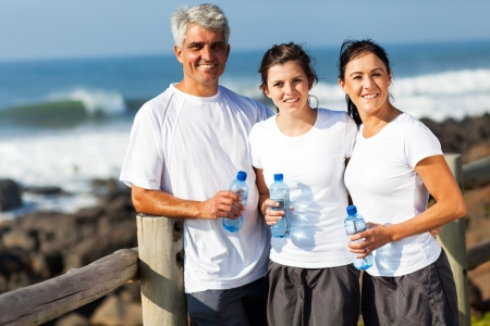 portrait of family relaxing after exercise at the beach photo