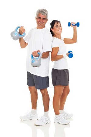 cheerful senior couple posing with various gym equipment on white background photo
