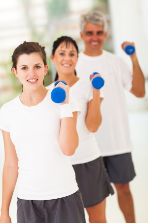 family exercise: line up of fit family exercising with dumbbells