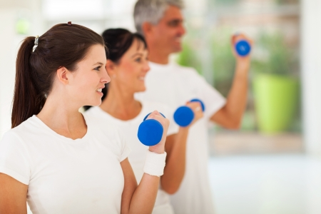 home gym: side view of fit family exercising with dumbbells at home Stock Photo