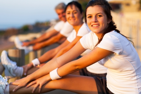 senior adult man: young girl stretching her leg two warm up before exercise at the beach Stock Photo