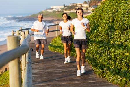 madre trabajando: activa de la familia corriendo por la playa por la mañana Foto de archivo