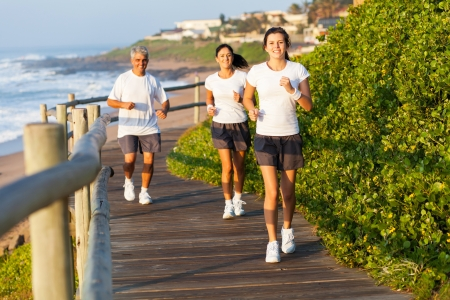 family exercise: active family running by the beach in the morning
