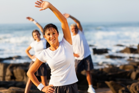 healthy senior woman exercising with family at the beach photo