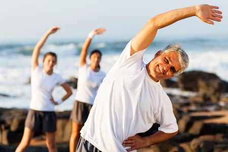 happy mid age man exercising at the beach with his family photo