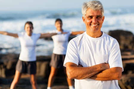 fit mature man on beach with family exercising on background photo