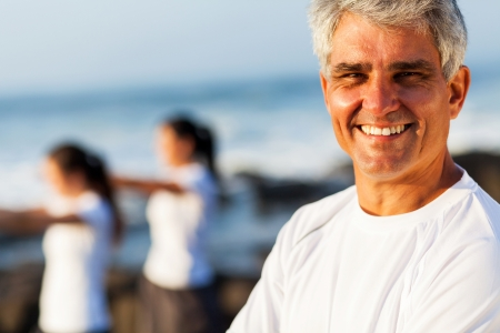smiling handsome active senior man posing at the beach with family photo