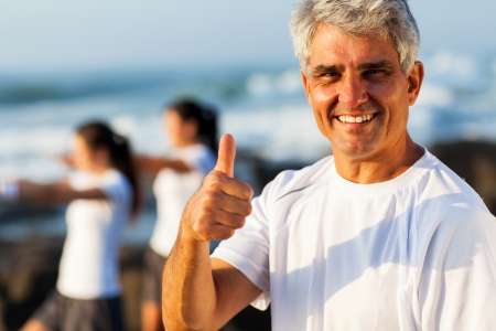middle aged men: active mature man giving thumb up on beach with family exercising on background Stock Photo