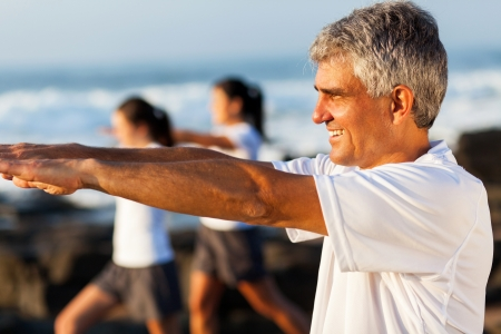 side view of healthy middle aged man exercising with family at the beach photo