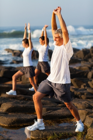 middle aged man exercising with his family at the beach photo