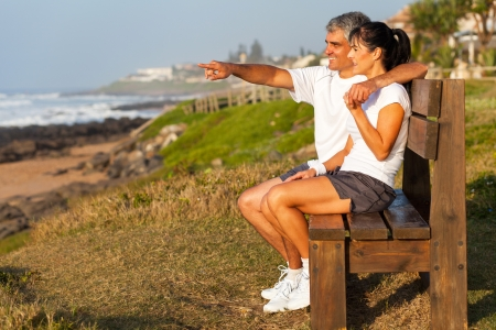 happy mature couple: fit middle aged husband and wife at beach in the morning