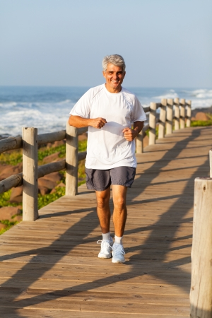 senior exercising: active happy middle aged man jogging at the beach in the morning