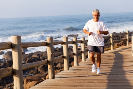 cheerful fit senior man running at the beach in the morning photo