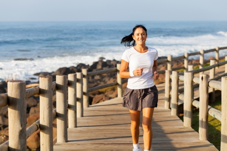 fit mid age woman jogging at the beach in the morning photo