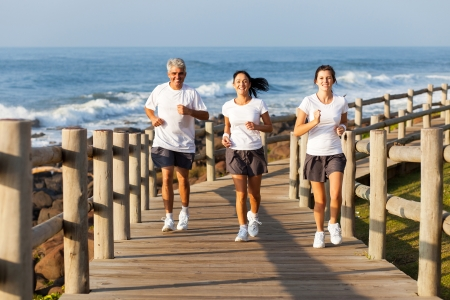 cheerful fit family jogging at the beach in the morning photo