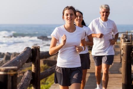 hombres haciendo ejercicio: feliz familia sana trotar en la playa por la mañana Foto de archivo