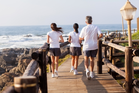 rear view of active family jogging on beach together in the morning  photo