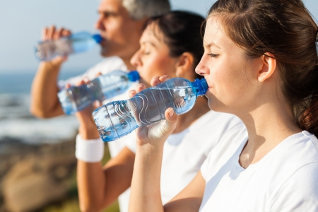 man drinking water: active family drinking water after jogging in the morning