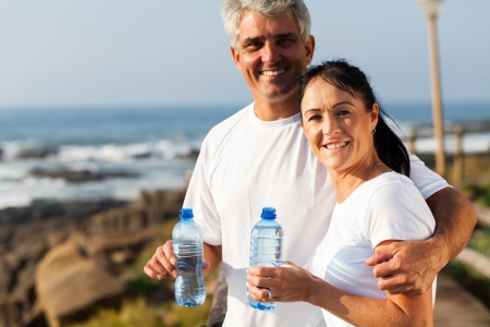 fit mature couple drinking water at the beach after exercise photo