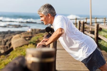 hombres haciendo ejercicio: Hombre mayor apto que ejercita en la playa por la mañana