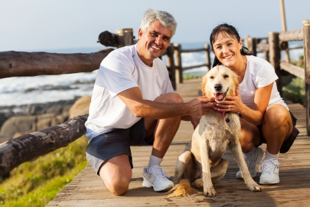 fit couple: sporty middle aged couple and pet dog at the beach in the morning Stock Photo