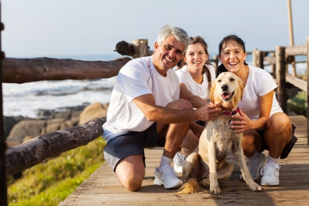 couple exercising: sporty family and their pet dog at the beach in the morning Stock Photo