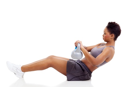 young african woman working out using kettle bell on white background photo