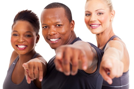 smiling group of gym instructors pointing at the camera on white background photo