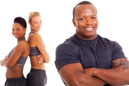 cheerful african male personal trainer and two gym members on background photo
