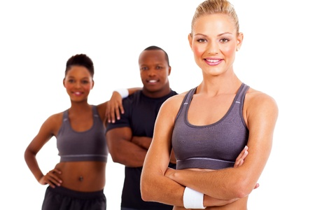 man working out: happy sporty woman with arms folded and gym members on background Stock Photo