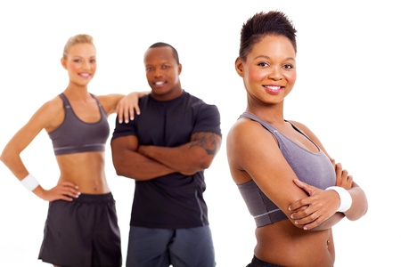 man working out: beautiful fit african woman in sportswear with two instructors on background