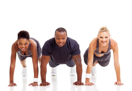 pushups: group of fit people doing pushups on white background Stock Photo