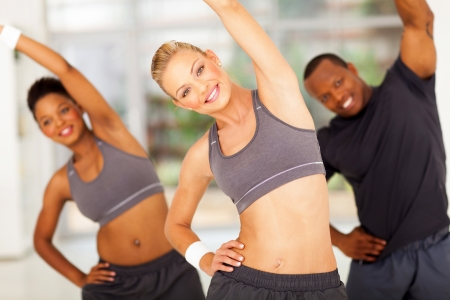 personal trainer: pretty personal trainer exercise with two africans on background