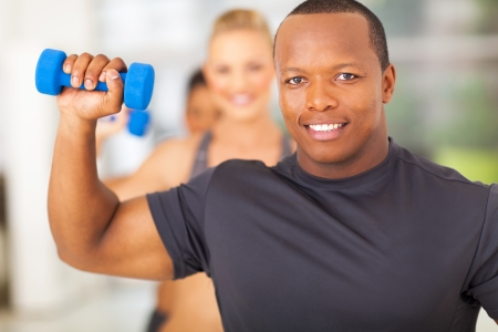 happy african man exercising in gym with dumbbell photo