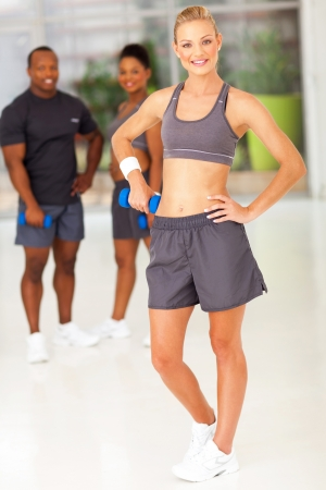 slim sporty woman posing with friends in gym Stock Photo - 19588778