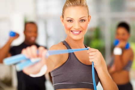 smiling woman exercise in gym with jumping rope photo