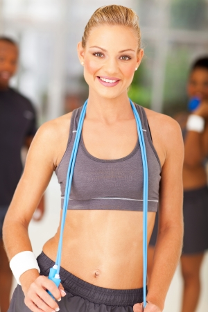 healthy fit woman with jump rope around her neck photo