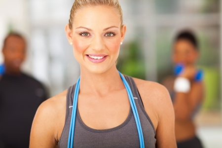 cheerful athletic woman with jump rope around her neck photo