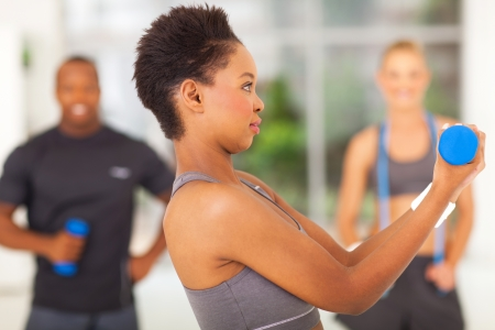 shaping: side view of african american woman lifting dumbbell with two hands
