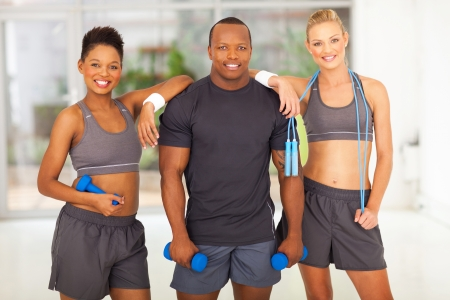 black woman white man: group of diversity people holding various gym equipment after exercise