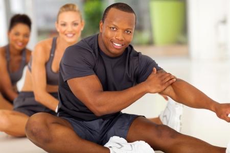 растягивание: Счастливый афро человек с командой растяжения до тренировки