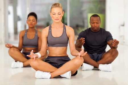 man meditating: group of young fit people meditating in a gym class
