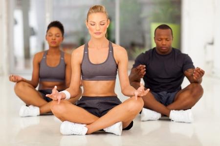 mujer meditando: grupo de j�venes en forma de personas meditando en una clase de gimnasia