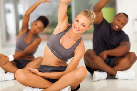 group of healthy people stretching at the gym photo