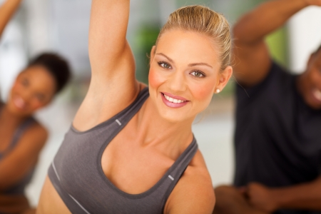 group fitness: beautiful fit woman stretching in gym with friends